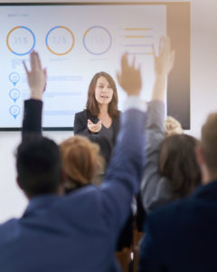 image of business people raising hands in classroom setting